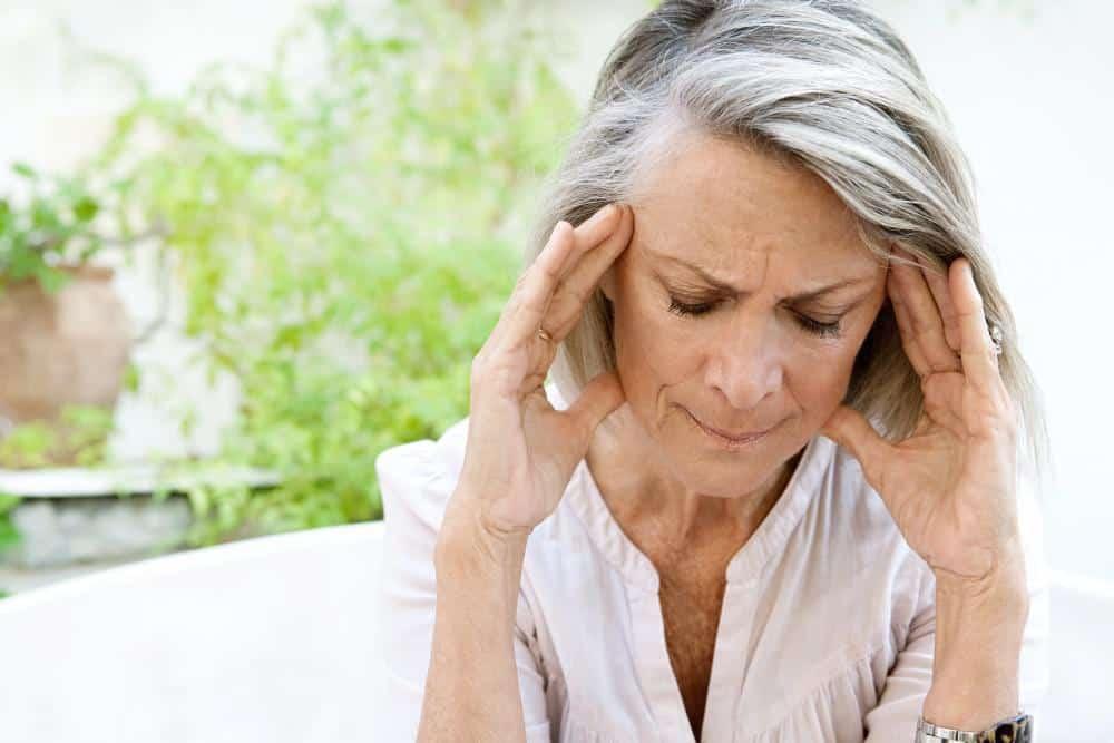 woman holding head with Chronic Sinusitis