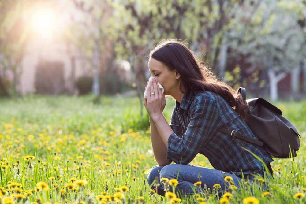 woman sneezing with allergies in flower field