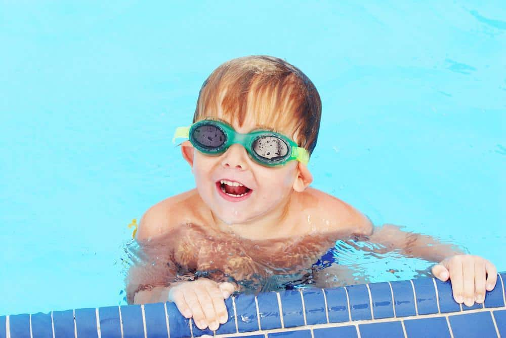 Child swimming int he pool smiling